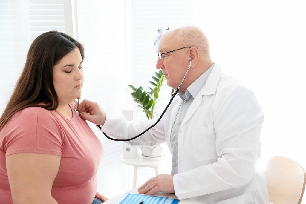 a doctor listening to an overweight woman's heartbeat during a weight loss consultation